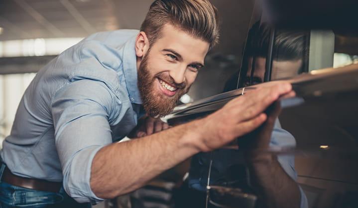 Hombre mirando admirado su auto nuevo comprado con un préstamo para autos